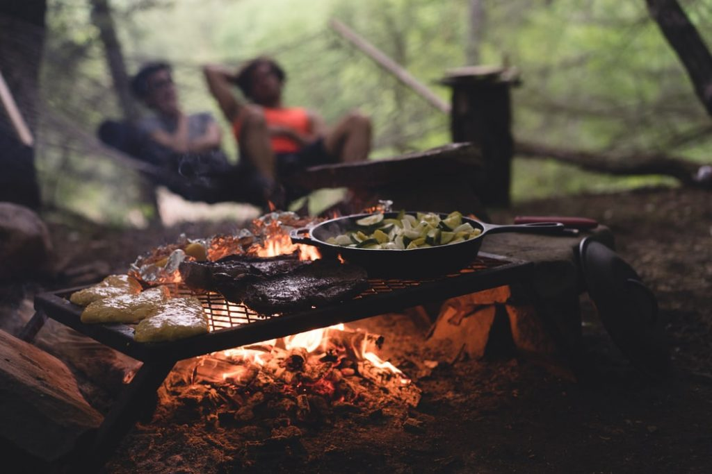 couple in hammock camping with food on the campfire